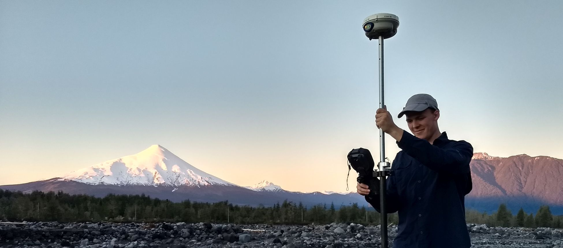 Student with equipment in front of a snow capped mountain
