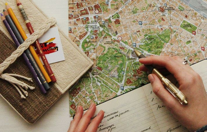 map and hands writing in a notebook